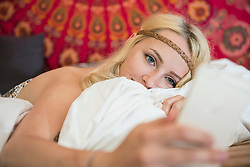 Beautiful young woman using smart phone in the bedroom, Bavaria, Germany