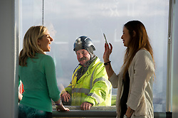 **PICTURES STRICTLY EMBARGOED INTIL 00:01 HOURS FRIDAY 11 JANUARY 2013** © London News Pictures. London, UK.  A workman on the outside of the The Shard watches a young woman pose for a photograph  during a media preview of the viewing level of The Shard building in London ahead of the public opening of 'A View From The Shard' on February 1, 2013. The public can view a 360 degree view of the capital from the 72nd floor of Western Europe's tallest building which stands at 800ft (244m).  Photo credit : Ben Cawthra/LNP