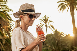 Chic mature blond woman holiday glamorous cocktail