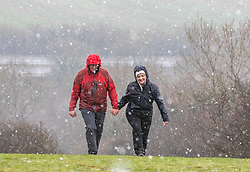 © Licensed to London News Pictures. 28/12/2020. Berkshire, UK. A couple brave the sleet, snow and cold as they hike up Beacon Hill near Newbury, Berkshire this afternoon as temperatures dropped to -3c in the South East today. The Met Office has issued a yellow weather warning for snow and ice for much of the country with heavy snow falls in Hampshire, Berkshire and the West Country. Photo credit: Alex Lentati/LNP