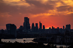 © Licensed to London News Pictures. 01/06/2021. London, UK. The sun sets behind the City of London on the first day of meteorological summer, as warm weather continues across much of the United Kingdom. Photo credit: Rob Pinney/LNP