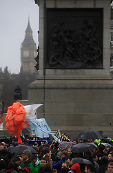 © Licensed to London News Pictures 13/04/2013.A large Thatcher motif, with hair made from Sainsbury's plastic bags, enters Trafalgar Square during an anti-Thatcher rally, following her death last week..London, UK.Photo credit: Anna Branthwaite/LNP