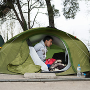 A young man from Iraq waking up in his tent in the railway station of Idomeni. Many people decided to live away from the transit camp where the conditions are appalling. <br /> <br /> Thousands of refugees are stranded in Idomeni unable to cross the border. The facilities here are stretched to the limit and the conditions are appalling. It's raining, it's cold there is mud everywhere and there is no hope that the border will open anytime soon.