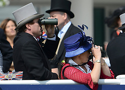 © Licensed to London News Pictures. 02/06/2012. London, UK. A couple watch the races. HRH Queen Elizabeth at The Investic Derby Festival today 2nd June 2012. The Royal Jubilee celebrations. Great Britain is celebrating the 60th  anniversary of the countries Monarch HRH Queen Elizabeth II accession to the throne this weekend Photo credit : Stephen Simpson/LNP