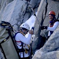 BAFFIN ISLAND, CANADA. John Catto films Greg Child hauling heavy load up Great Sail Peak.