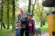 Friendly Polish woman park attendant age 55 with children bicyclers wearing helmets. Paderewski Park Rzeczyca Central Poland