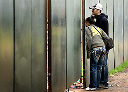 © Licensed to London News Pictures. 06/06/2012. London, UK. A man and a woman look through a security wall into the construction site in front of Buckingham Palace. Workmen begin the task of deconstructing the stages and scaffolding platforms put in place for the celebrations.  The Royal Jubilee celebrations. Great Britain is celebrating the 60th  anniversary of the countries Monarch HRH Queen Elizabeth II accession to the throne this weekend Photo credit : Stephen Simpson/LNP