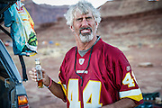 SHOT 10/16/16 6:12:15 PM - Paul Hobson of Steamboat Springs, Co. takes a swig of rum while camping at the Airport camp spot on the White Rim. The White Rim is a  mountain biking trip in Canyonlands National Park just outside of Moab, Utah. The White Rim Road is a 71.2-mile-long unpaved four-wheel drive road that traverses the top of the White Rim Sandstone formation below the Island in the Sky mesa of Canyonlands National Park in southern Utah in the United States. The road was constructed in the 1950s by the Atomic Energy Commission to provide access for individual prospectors intent on mining uranium deposits for use in nuclear weapons production during the Cold War. Four-wheel drive vehicles and mountain bikes are the most common modes of transport though horseback riding and hiking are also permitted.<br /> (Photo by Marc Piscotty / © 2016)