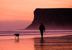 © Licensed to London News Pictures. <br /> 30/10/2016. <br /> Saltburn-by-the-Sea, UK.  <br /> A man walks his dog along the wet sand as the sun begins to rise over Saltburn-by-the-Sea on the north east coast of England.<br /> Photo credit: Ian Forsyth/LNP