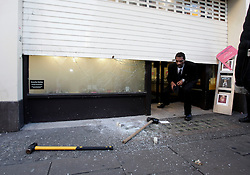© Licensed to London News Pictures. 20/12/2011. London, United Kingdom .A security guard checks out the front of the store after the attempted robbery on a jewellery shop on Oxford Street by persons on two motorbikes..Photo credit : Chris Winter/LNP