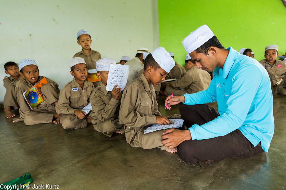 10 JULY 2013 - PATTANI, PATTANI, THAILAND: Students study the Koran at a private Muslim school in Pattani, Thailand. Many Muslim parents prefer to send their children to Muslim private schools because they are safer (public schools have been attacked by Muslim insurgents), the Muslim schools teach an Islam centric curriculum and teach what many in Pattani consider a more accurate version of Pattani history.   PHOTO BY JACK KURTZ