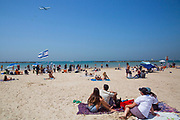 People on the beach watch as an IAI cargo Boeing 777 performs a flyover in Tel-Aviv, Israel April 15, 2021. People gathered in their masses at Tel-Aviv's shore line as the Jewish state celebrates 73 years to it's establishment. As vast percentage of the population are vaccinated, celebrations were able to take place in a some what ordinary manner.Starting Sunday April 18, 2021, it will no longer be mandatory to wear a protective mask in open spaces throughout the country.