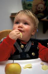 Toddler eating healthy apple in highchair UK