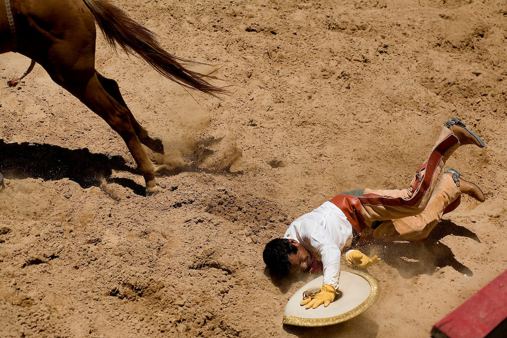 Victoriano Flores Sr., right, falls to the ground after a bumpy ride during the Jineteo de Yegua, or bareback riding, at a charreada in San Antonio.  Charros receive points base on their style and staying power unlike American rodeo's 8-second standard.