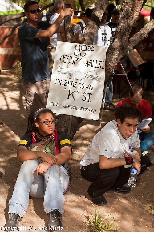 """22 OCTOBER 2011 - PHOENIX, AZ:    Occupy Phoenix protesters during the General Assembly at Occupy Phoenix Saturday. The demonstrations at Occupy Phoenix, AZ, entered their second week Saturday. About 50 people are staying in Cesar Chavez Plaza, in the heart of downtown. The crowd grows in the evening and on weekends. Protesters have coordinated their actions with police and have gotten permission from the city to set up shade shelters and sleep in the park, but without tents or sleeping bags, which is considered """"urban camping,"""" instead protesters are sleeping on the sidewalk.      PHOTO BY JACK KURTZ"""