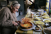 In her farmhouse kitchen in the village of Adamka, in central Poland, 93-year-old Maria Kwiatkowska, Borys's grandmother, slices the cheesecake she baked for the traditional family gathering on All Saints Day. After visiting the graves of their relatives in the local cemetery, her children and grandchildren descend on her for a splendid lunch of noodle soup with cabbage and carrots, pork roast stuffed with prunes, pickled pumpkin, a fruit-nut roll, and cheesecake. Hungry Planet: What the World Eats (p. 250). (MODEL RELEASED IMAGE).