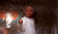 T.J. Jones, 4, writes in a fogged up window at his grandmothers house off Guerlain Way in Montclair, due to the rain and cool weather.