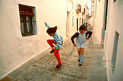 SPAIN, ANDALUSIA VEJER DE LA FRONTERA; near Cadiz, a traditional Moorish style village or 'pueblo blanco'; girls jumping rope