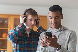 Young friend holding mobile phone while other friend  wearing headphones and listening to music