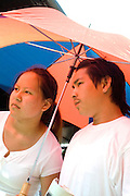 Hmong couple under umbrella protecting them from intense sun rays. Hmong Sports Festival McMurray Field St Paul Minnesota USA