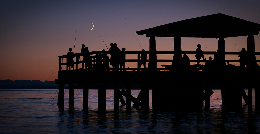 The crescent moon and planet Jupiter in the evening sky over people fishing at dusk in Sechelt, BC. (2015)
