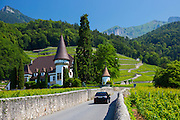 Suburu hatchback car passes wine estate, Chateau Maison Blanche, at Yvorne in the Chablais region of Switzerland