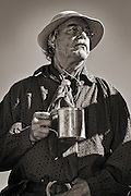 Buckskinner with his tin cup taking a break at Historic Fort Bridger in southern Wyoming at a yearly Mountain Man Rendezvous.