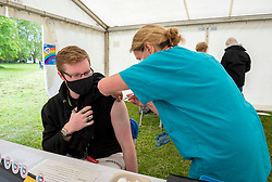 © Licensed to London News Pictures; 19/06/2021; Bristol, UK. BEN WILSON receives a Pfizer vaccination against Covid-19 coronavirus from nurse GAIL DANIEL at a pop-up vaccination clinic in Bristol's Eastville Park which is being run by the Bristol CCG. The queue for jabs, with many of them young people, stretched half way down the park as walk-in vaccine clinics open in England in a major push to offer coronavirus jabs to all remaining adults to counter the recent increase in cases of covid with the spread of the Delta variant. Photo credit: Simon Chapman/LNP.