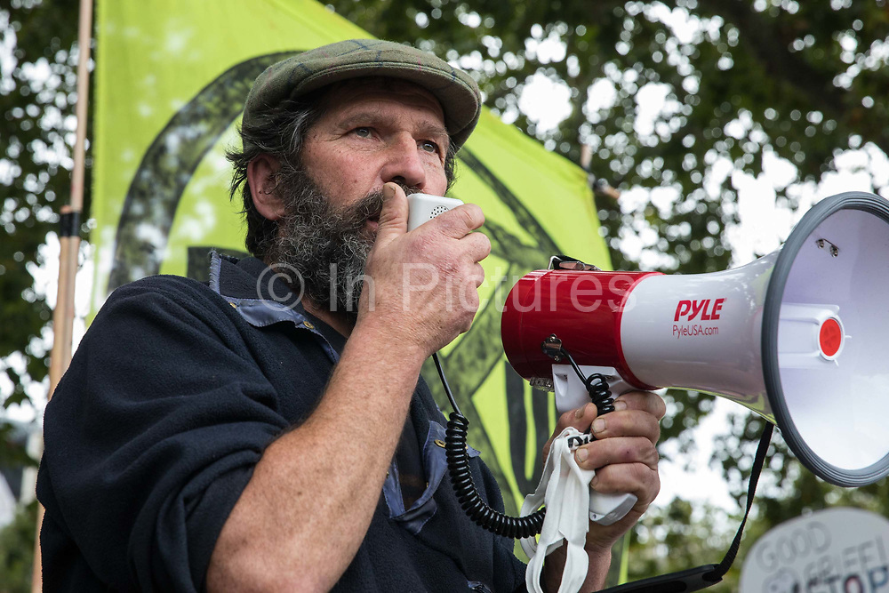 Longstanding tree protector Mark Keir from HS2 Rebellion, an umbrella campaign group comprising longstanding campaigners against the HS2 high-speed rail link as well as Extinction Rebellion activists, addresses a protest rally in Parliament Square on 4 September 2020 in London, United Kingdom. The rally, and a later protest action at the Department of Transport during which activists glued themselves to the doors and pavement outside and sprayed fake blood around the entrance, coincided with an announcement by HS2 Ltd that construction of the controversial £106bn high-speed rail link will now commence.
