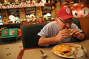 """Trucker Tom Lang takes a break from the road to focus on a beef sandwich at """"R"""" Place restaurant at the RA Travel Centers of America in Morris, Illinois."""