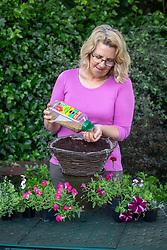 Planting up a hanging basket. Adding slow release plant food.