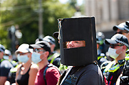 A man is seen wearing a Ned Kelly helmet during the Melbourne Freedom Rally at Parliament House. Police move into position on the steps of state parliament ahead of a planed protest. The groups who have organised the many Freedom Day protests over the last 3 months, attempted to march on State Parliament during Melbourne Cup Day demanding the sacking of Premier Daniel Andrews for the lockdown and attacks on their civil liberties. Police met with the protester's with significant force despite the city having had zero cases for five days. (Photo by Dave Hewison/Speed Media)