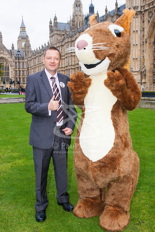 """Nature campaigners accompanied by a  giant red squirrel, Bob, urge MPs to """"Vote For Bob"""" during a photocall outside Parliament. Their aim is to get MPs to support nature in Britain. Pictured: Jason McCartney MP poses with Bob the red squirrel."""