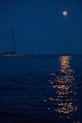 Camden, ME - 10 August 2014. The Supermoon over Camden, catamaran Zenyatta at anchor.