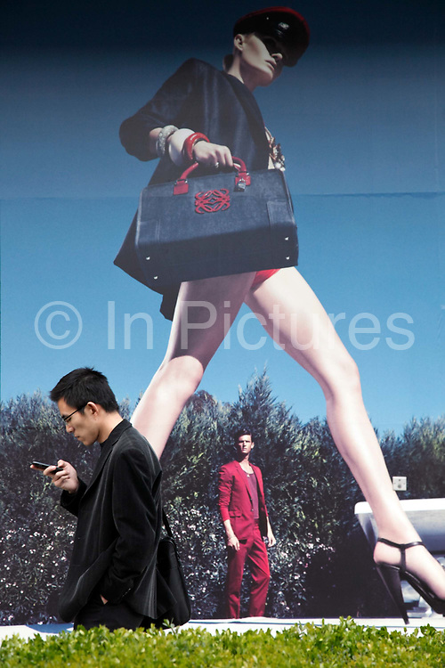 Pedestrians walk past an advertisement for luxury fashion  in Shanghai, China on 04 April, 2009.  As disposable income for China's rich continue to rise, China is now the biggest luxury goods market in the world, with sales passing a quarter of the global total and more than that of the united States in 2009.