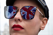 Anti Brexit pro Europe demonstrator has the Union Jack flag reflected in her sunglasses in Westminster on 26th March 2019 in London, England, United Kingdom. With the date of the UK leaving the European Union extended, the pro EU protest continues as MPs from all sides try to gain control of the process.