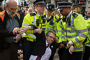 A legal observer puts an information sheet into the hand of an activist with Extinction Rebellion as hes arrested during the London protest about climate change in a blocked-off Oxford Circus , on 17th April 2019, in London, England.