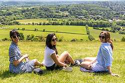 Licensed to London News Pictures. 05/06/2021. Dorking, UK. After the heavy rains yesterday, school friends from Kingston (L to R) Malti Vaghela, Izzy Khan and Nadia Saif all 30 enjoy the warm sunshine on Box Hill in Surrey as the fine June weather continues. The Met Office have forecast very warm weather for the South East and London with temperatures predicted to hit up to 24c for next week. Photo credit: Alex Lentati/LNP
