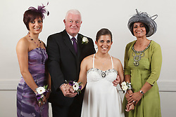 Bride who has cerebral palsy, with sister, mother and grandfather at wedding ceremony.