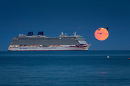 A helicopter passes the Harvest Moon as it rises above P&O Cruises' largest ship, Britannia sitting at anchor in Weymouth Bay. The cruise industry has suffered a complete shutdown during the covid-19 pandemic and many vessels are currently waiting at various anchorages around the coast of Great Britain and the world.<br /> Picture date Tuesday 1st September, 2020.<br /> Picture by Christopher Ison. Contact +447544 044177 chris@christopherison.com