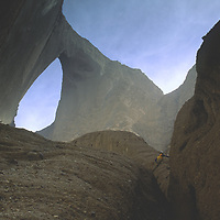 CHINA, Xinjiang.  Mountaineer Sam Lightner (MR) in slot canyons below Shipton's Arch in arid Kara Tagh Mts near Taklimakan Desert.