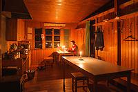 Candlelight illumintes room Singi mountain hut at night, Kungsleden trail, Lappland, Sweden