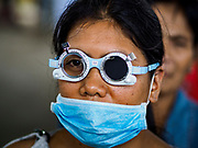 """22 JANUARY 2018 - GUINOBATAN, ALBAY, PHILIPPINES: A woman in an evacuation center in Guinobatan wears a face mask while she gets her eyes checked during a clinic at the shelter. Several communities in Guinobatan were hit ash falls from the eruptions of the Mayon volcano and many people wore face masks to protect themselves from the ash. There were a series of eruptions on the Mayon volcano near Legazpi Monday. The eruptions started Sunday night and continued through the day. At about midday the volcano sent a plume of ash and smoke towering over Camalig, the largest municipality near the volcano. The Philippine Institute of Volcanology and Seismology (PHIVOLCS) extended the six kilometer danger zone to eight kilometers and raised the alert level from three to four. This is the first time the alert level has been at four since 2009. A level four alert means a """"Hazardous Eruption is Imminent"""" and there is """"intense unrest"""" in the volcano. The Mayon volcano is the most active volcano in the Philippines. Sunday and Monday's eruptions caused ash falls in several communities but there were no known injuries.    PHOTO BY JACK KURTZ"""