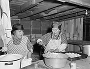 """9305-B7381-3.  Indians cooking at the last Feast of the First Salmon at Celilo Village before Celilo Falls were permanently submerged by the backwater of The Dalles Dam. Photo taken April 29, 1956. Left is Hannah Sohappy Yallup, right is Catherine Cushingway (mother of Nathan """"8-Ball"""" Jim)."""
