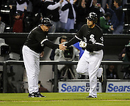 CHICAGO - APRIL 23:  Third base coach Jeff Cox #6 greets Carlos Quentin #20 of the Chicago White Sox after Quentin hit a home run in the second inning against the Seattle Mariners on April 23, 2010 at U.S. Cellular Field in Chicago, Illinois.  (Photo by Ron Vesely)