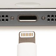 Closeup of the charging port on the bottom of a smartphone, with the charging connector in the foreground.