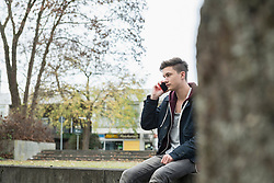Young man talking on mobile phone and sitting on ledge, Munich, Bavaria, Germany
