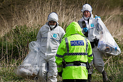 © licensed to London News Pictures. Leigh, Greater Manchester, UK  10/04/2012. Forensic officers photograph the scene where the burned body of a man has been discovered. A tent has been erected in a wooded area near to Pennington Road, adjascent to a brook. Several police are at the scene. Photo credit should read Joel Goodman/LNP