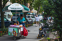 A Celicioso Coco Helado (delicious coconut icecream) vendor scoops a small portion for the man on the bench. Although a small scoop is $2.50 and the man said before hand that he had only $1.80 she gave it to him anyway with a smile.  Seen on Columbus Avenue and 77th street.