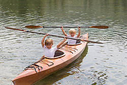 two boys holding paddles over their heads while sitting in a kayak on a lake